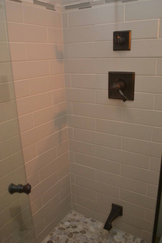 Grey matte subway tile subway with bronze fixtures and river rock floor