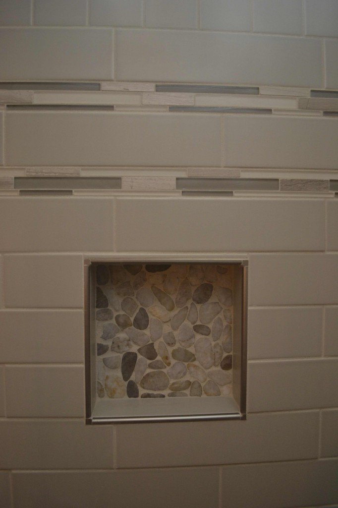 Shower niche with river rock tile