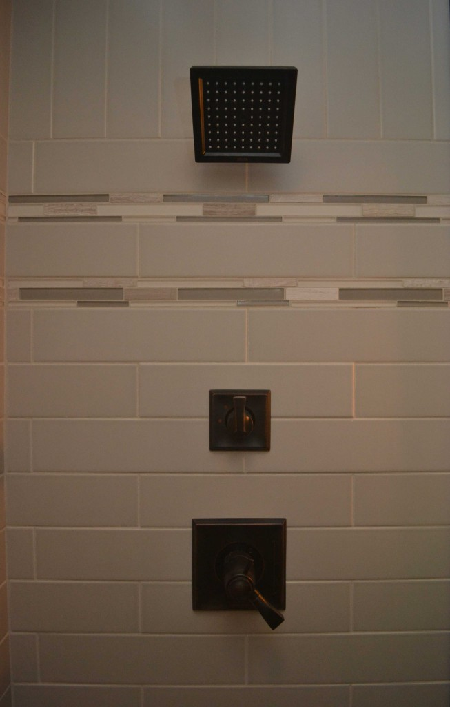 Close up of subway tile and border tile with bronze shower fixtures