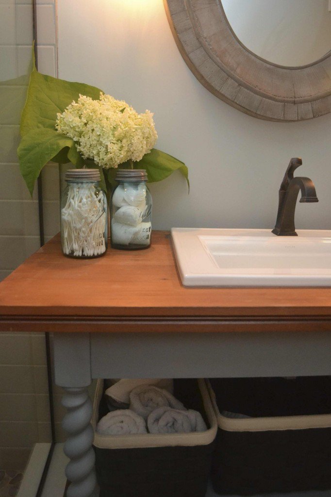 Bronze faucet with repurposed antique library table vanity and reclaimed wood mirror