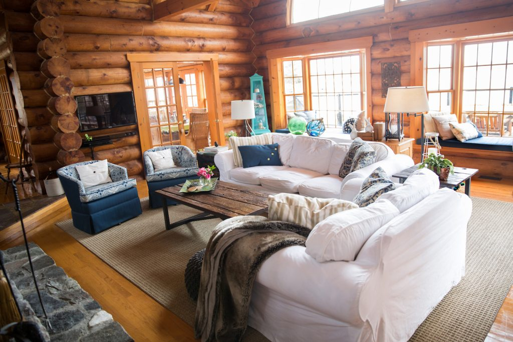 log home living room with white slipcovered sofas