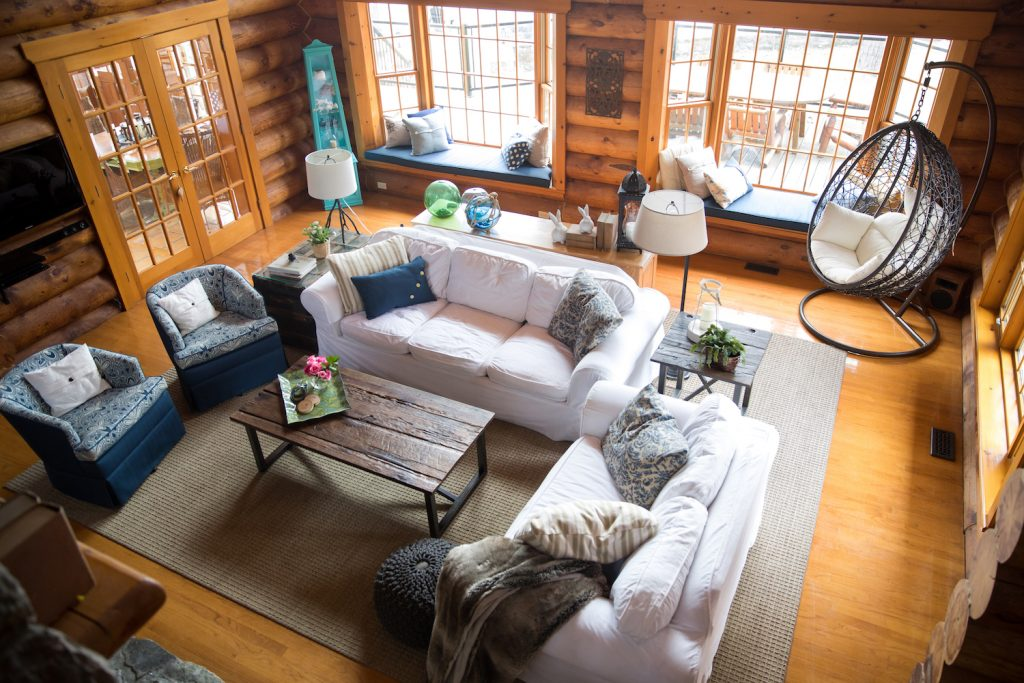 Log home living room with white sofas and blue swivel chairs