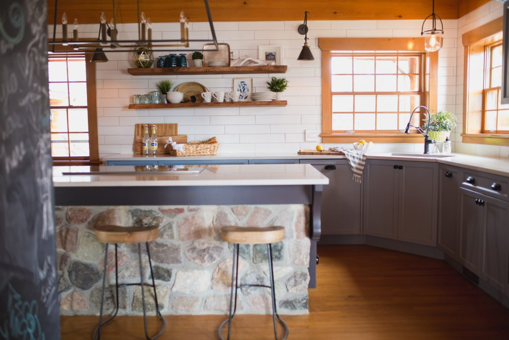 log cottage kitchen with blue cabinetry, stone island and open shelving