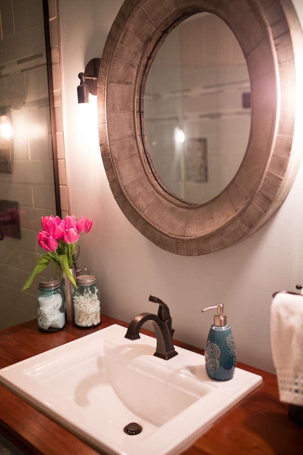 Round reclaimed wood mirror with bronze bath faucet and lighting
