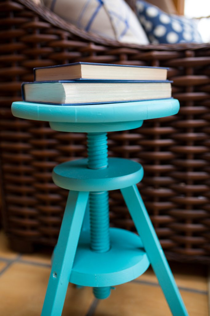 Turquoise piano stool used as table in sunroom